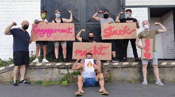 Menschengruppe mit Alltagsmasken hält den auf Pappe geschriebenen Spruch »Engagement macht stark!«.