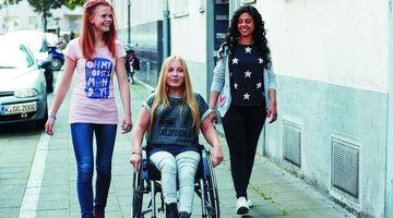 Drei Jugendliche gehen einen engen Weg zwischen einer Häuserwand und parkenden Autos entlang. Eine Person sitzt im Rollstuhl, die anderen beiden laufen neben ihr.