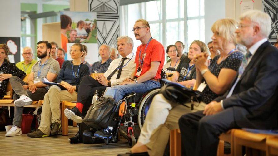 Eine Gruppe von Menschen in einem großen Raum. Die Personen blicken auf eine Bühne. In der Mitte ist ein Mann im Rollstuhl im Fokus.