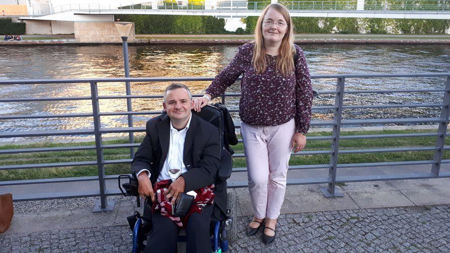 Wolfram Giese sitzt im Rollstuhl, daneben steht eine Frau. Beide blicken in die Kamera, im Hintergrund ist ein Fluss und eine Brücke zu sehen.