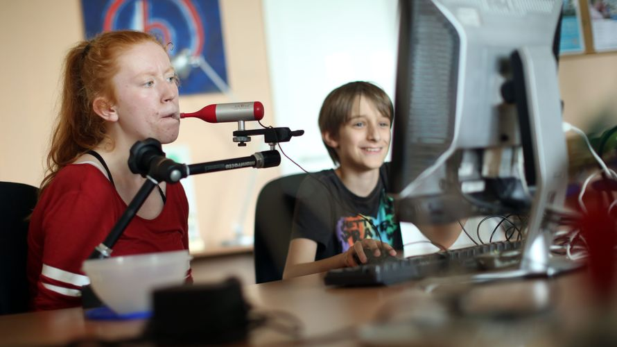 Zwei Schüler*innen sitzen vor einem PC, um sie herum sieht man technisches Equipment. Sie nehmen eine barrierefreie Sendung für ein Schulprojekt auf, das Mädchen spricht dazu in ein Aufnahmegerät.