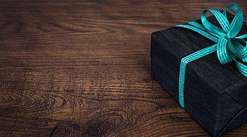 Schwarzes Geschenkpaket mit hellblauer Schleife auf dunklem Holztisch.
