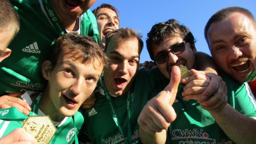 Eine Gruppe Männer beugt sich jubelnd in die Kamera und hält Medaillen hoch. Alle Männer tragen das gleiche grüne Mannschaftstrikot. Ein Mann aus der Gruppe zeigt einen Daumen hoch.